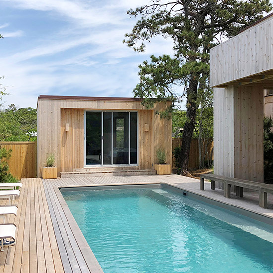 A restoration and expansion of a landmark modernist Fire Island house includes a new guest house, pool, exterior stair, entry pavilion, and landscaping.