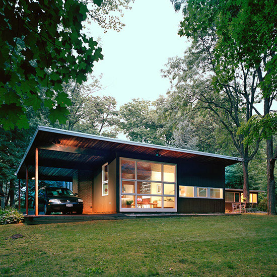 The renovation of this midcentury-modern house in the Palisades, NY included extensive glass window walls, new stone flooring, wood floors, and a renovated kitchen.