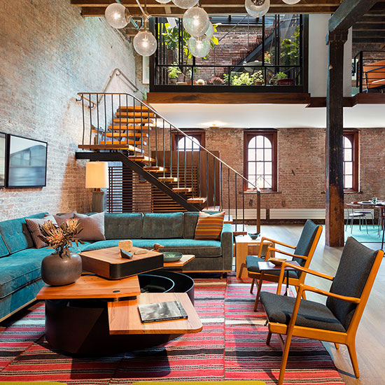A historic warehouse loft in Tribeca becomes a warm, open residence with curated midcentury furnishings, soft carpets and rich fabrics contrasting the industrial space.