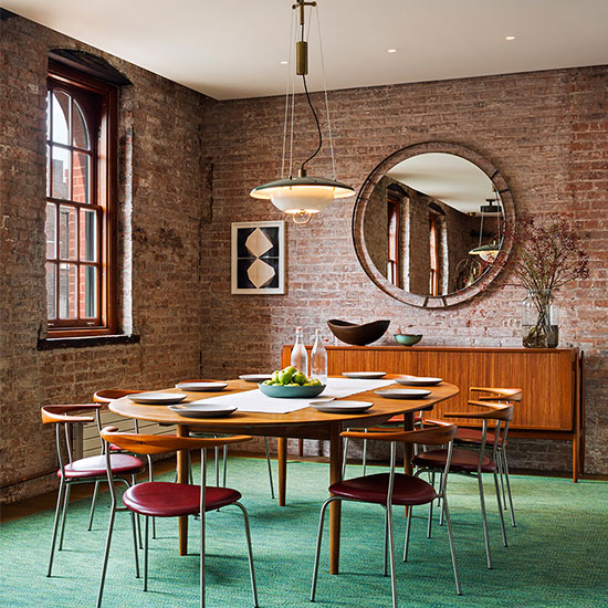 An 1884 former caviar warehouse loft in Tribeca becomes a warm, open residence with its curated vintage midcentury furnishings, soft carpets and rich fabrics contrasting the industrial steel and brick space.